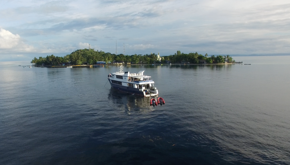 An aerial view of the Raja Ampat Aggressor docked near a remote island