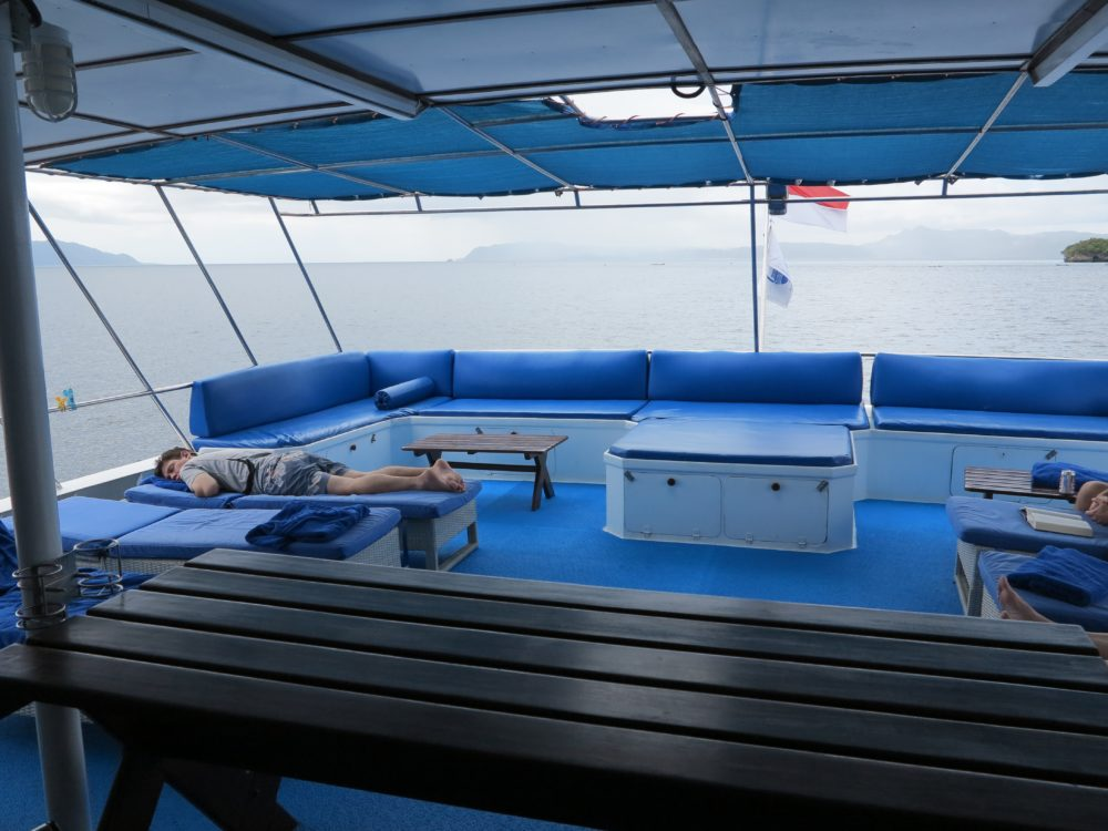 Raja Ampat Aggressor upper deck with one of the passengers laying on a blue deck chair