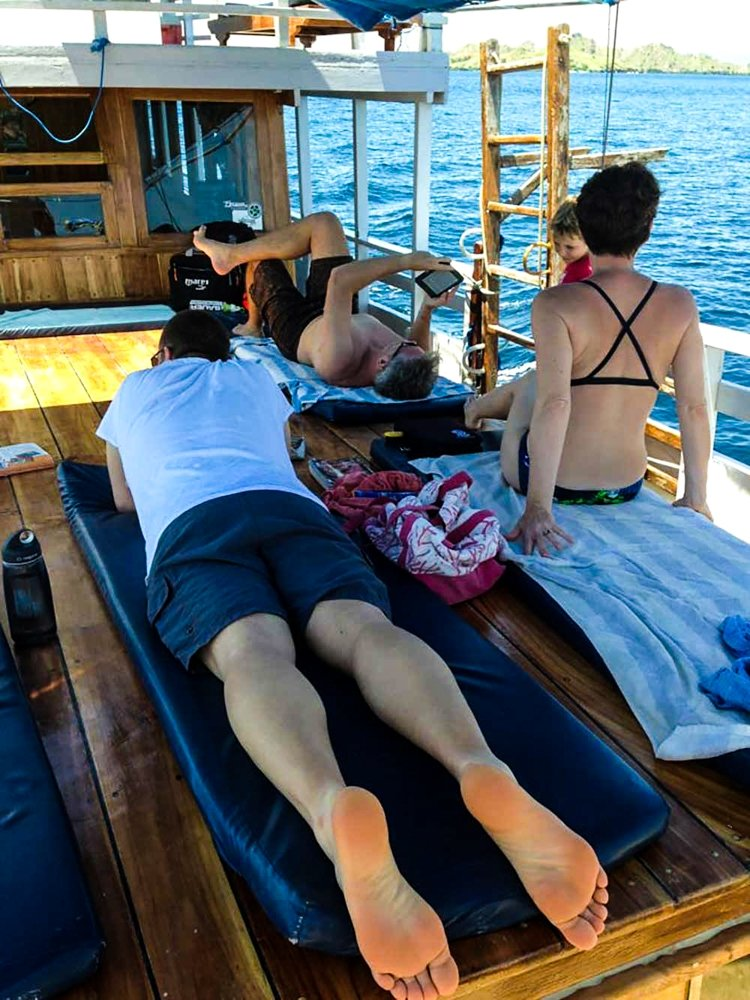 Diving Komodo National Park - the boat deck with people lying on the deck
