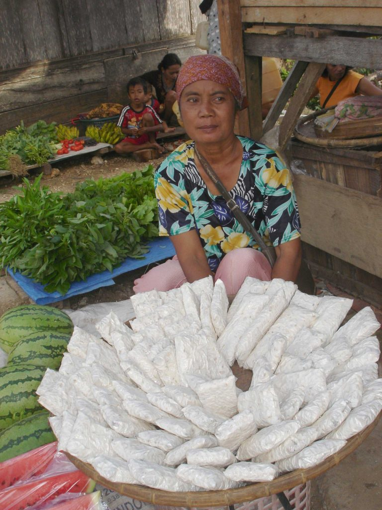 A woman sells tempeh at an Indonesian market