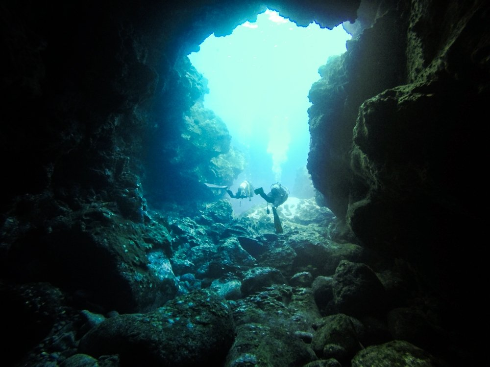 Halef scuba diving through an underwater cave on easter island