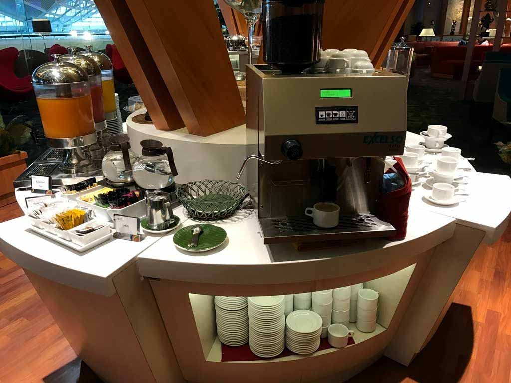 A coffee machine, tea selection, and juice dispensers at the Bali Premier Lounge