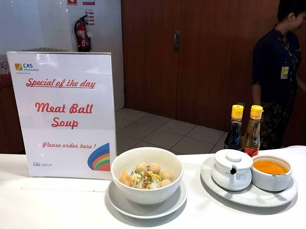 A sign that states 'Special of The Day: Meathball soup with a place setting and an example of the dish.