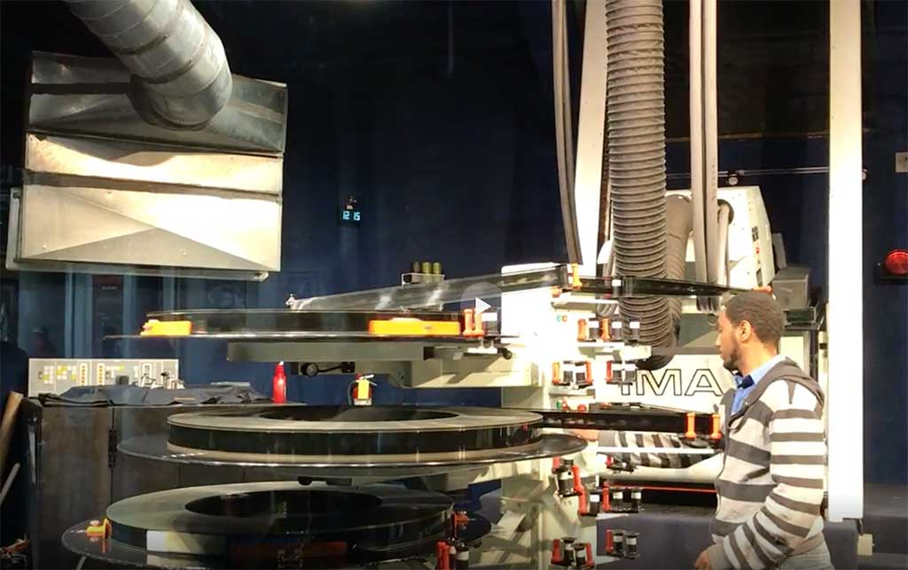 A worker weaves the film through the machinery at the IMAX theater