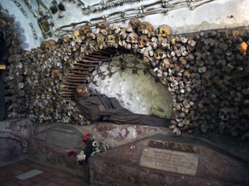 A capuchin monk skeleton inside the crypt with skulls surrounding it