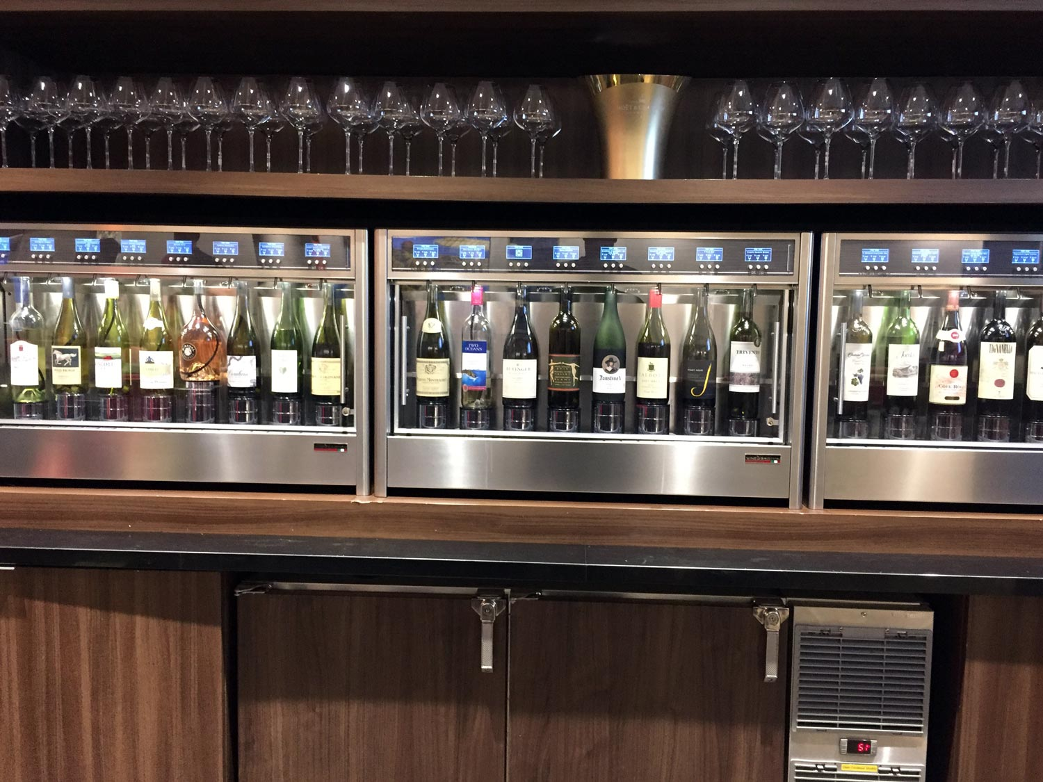 A row of wine bottles in an automatic dispenser at a Delta Sky Club
