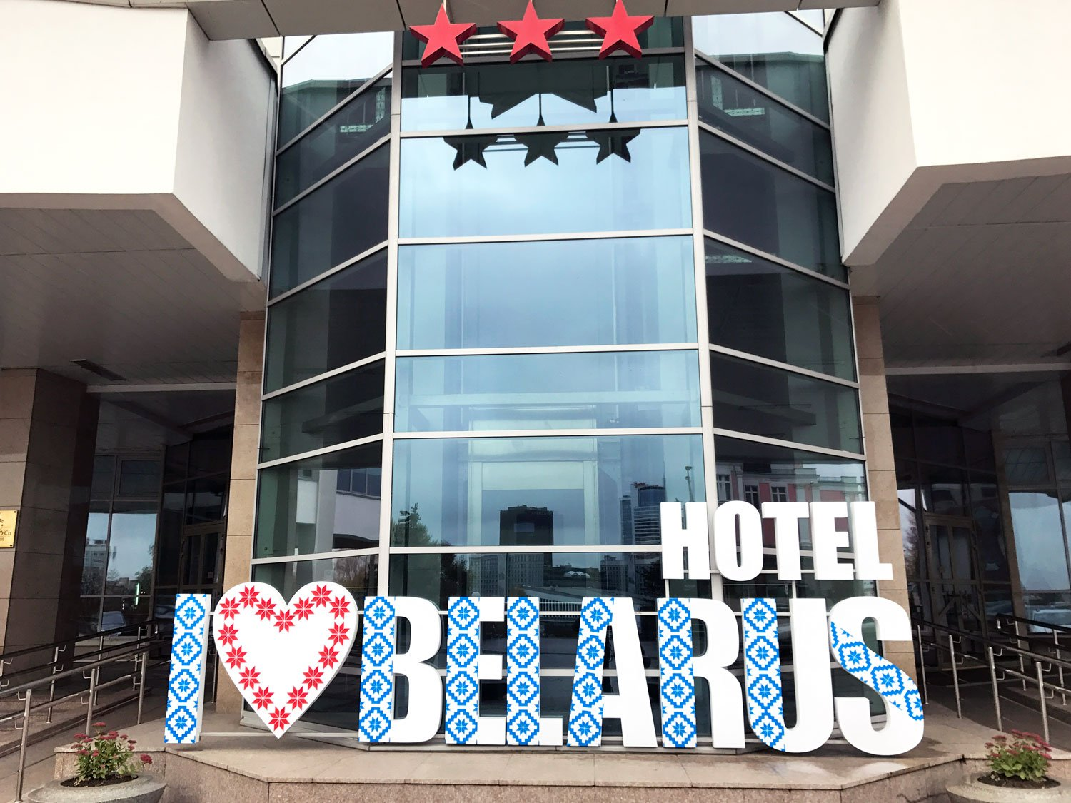 "Hotel Belarus with an I ""heart"" Hotel Belarus sign in front and three red stars, indicating the class of the hotel"