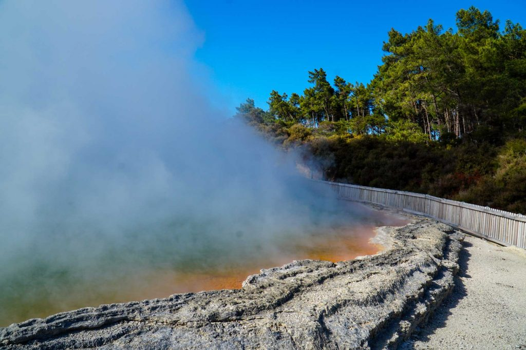 The shore of the Champagne Pool with orange rust-like mud and steam rising from the water