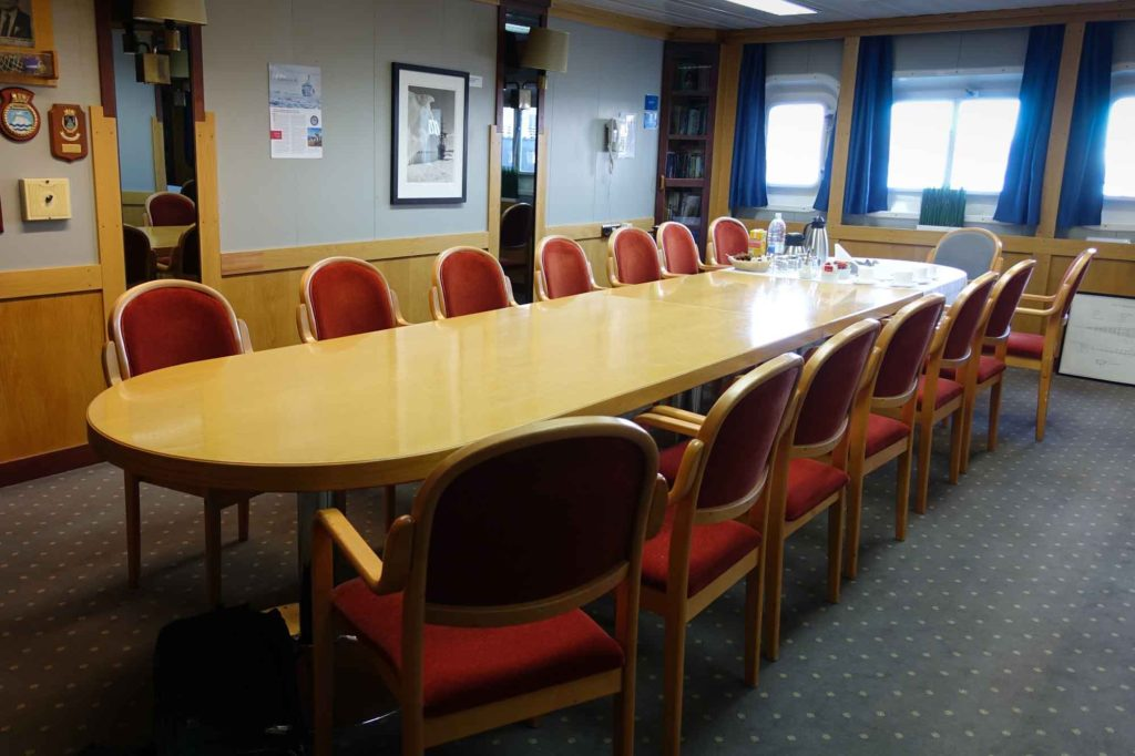 The library of the Akademik Ioffe. A long board room style table with windows looking out to the ocean.