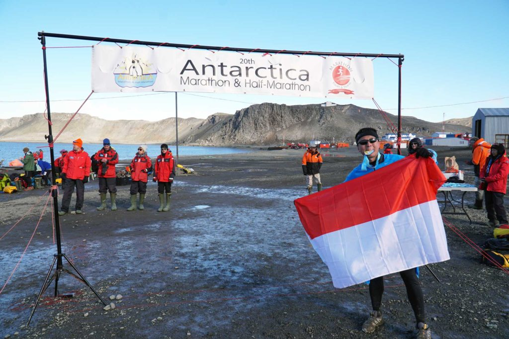 halef holding the indonesian flag at the antarctica marathon finish line