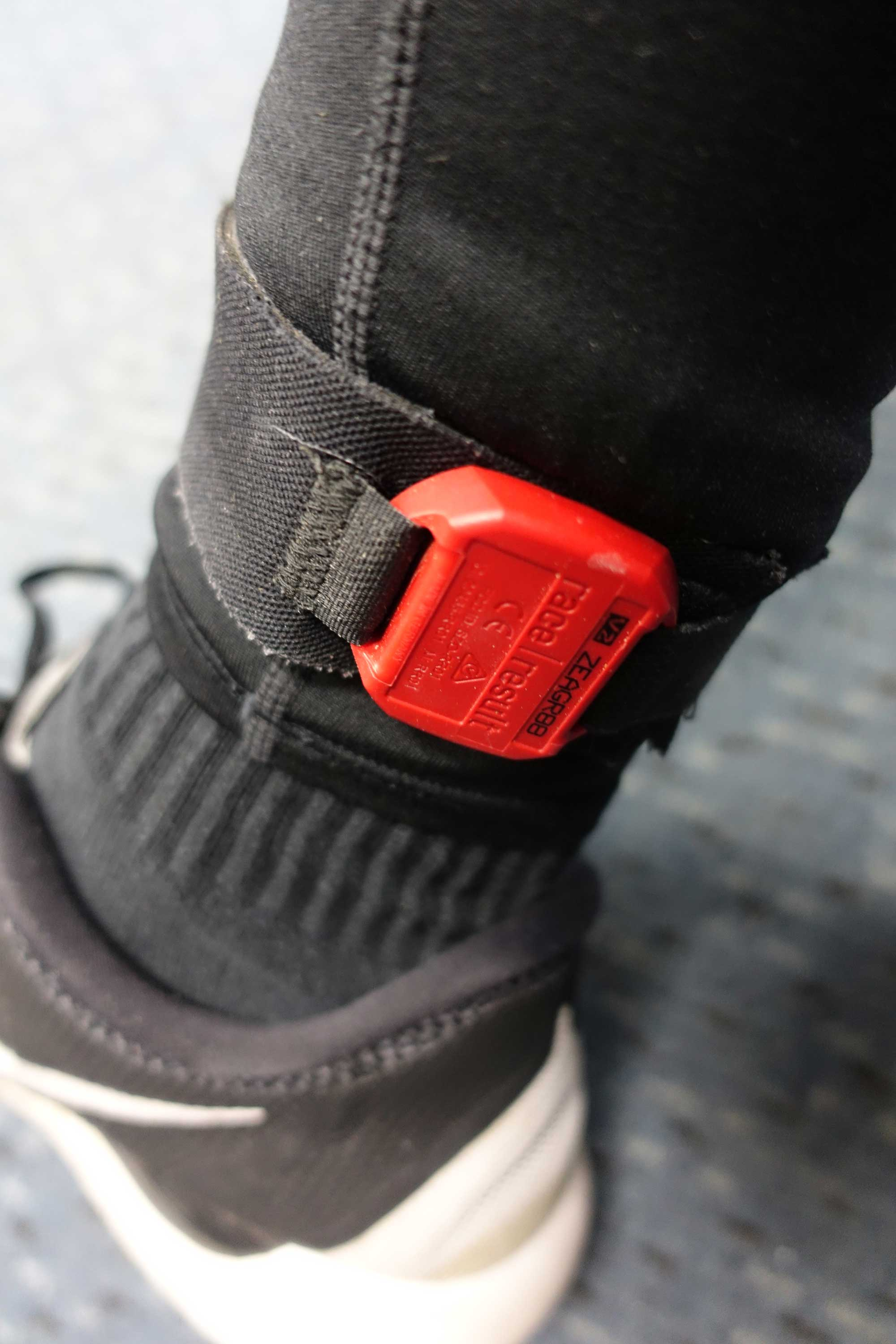 A red timing chip strapped to halef's ankle.