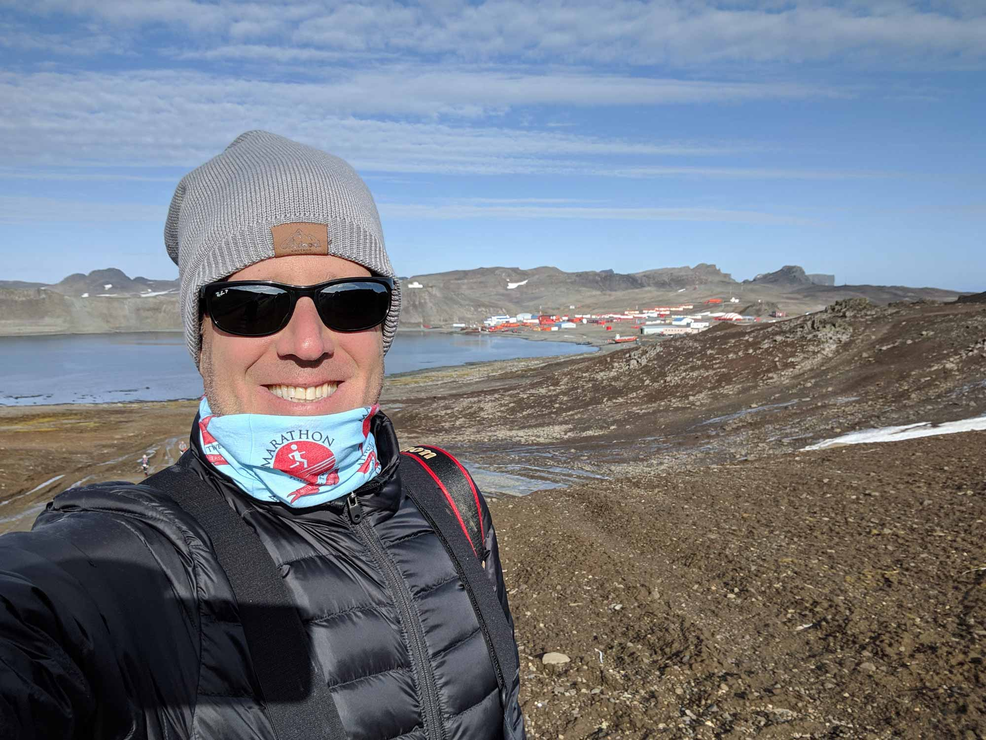 What to wear in antarctica in march when it's warm? Michael wearing just a small puff coat, a cap, and a neck gaiter. Very little snow in the background