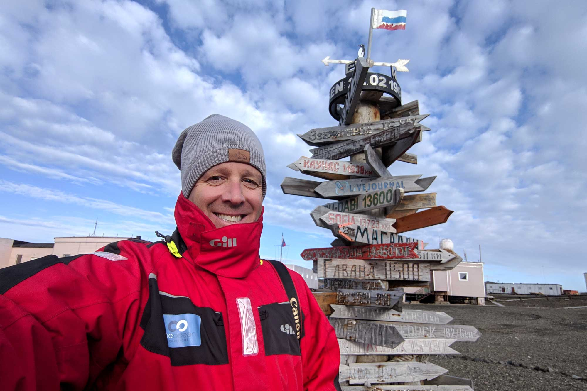 Michael standing in front of a signpost at the russian base on antarctica. The sign shows the distance to various cities in russia and around the world.