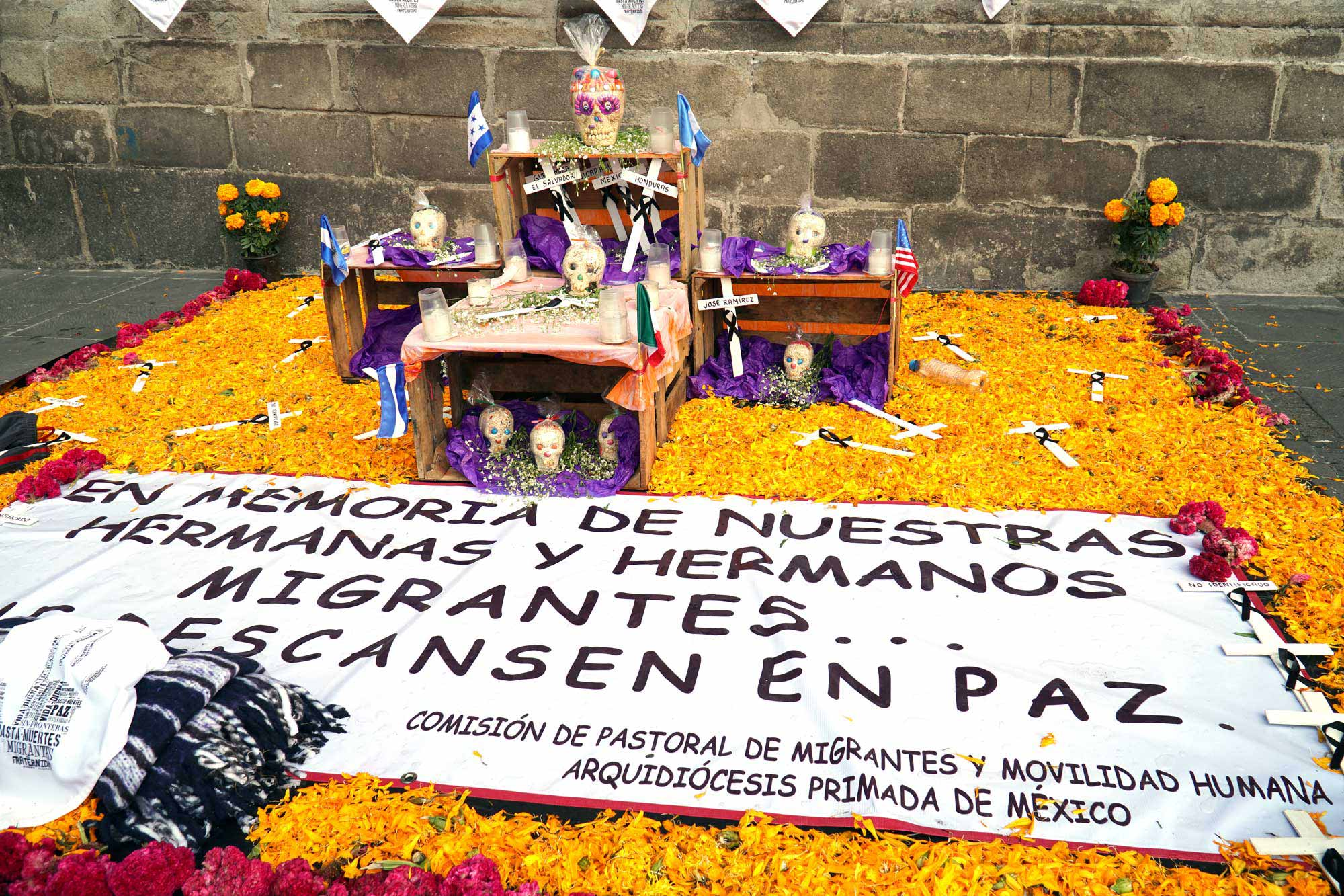 "a mexico city ofrenda outside the main cathedral which reads ""En memoria de nuestras hermanas y hermanos migrantes"" or ""In memory of our migrant sisters and brothers"""