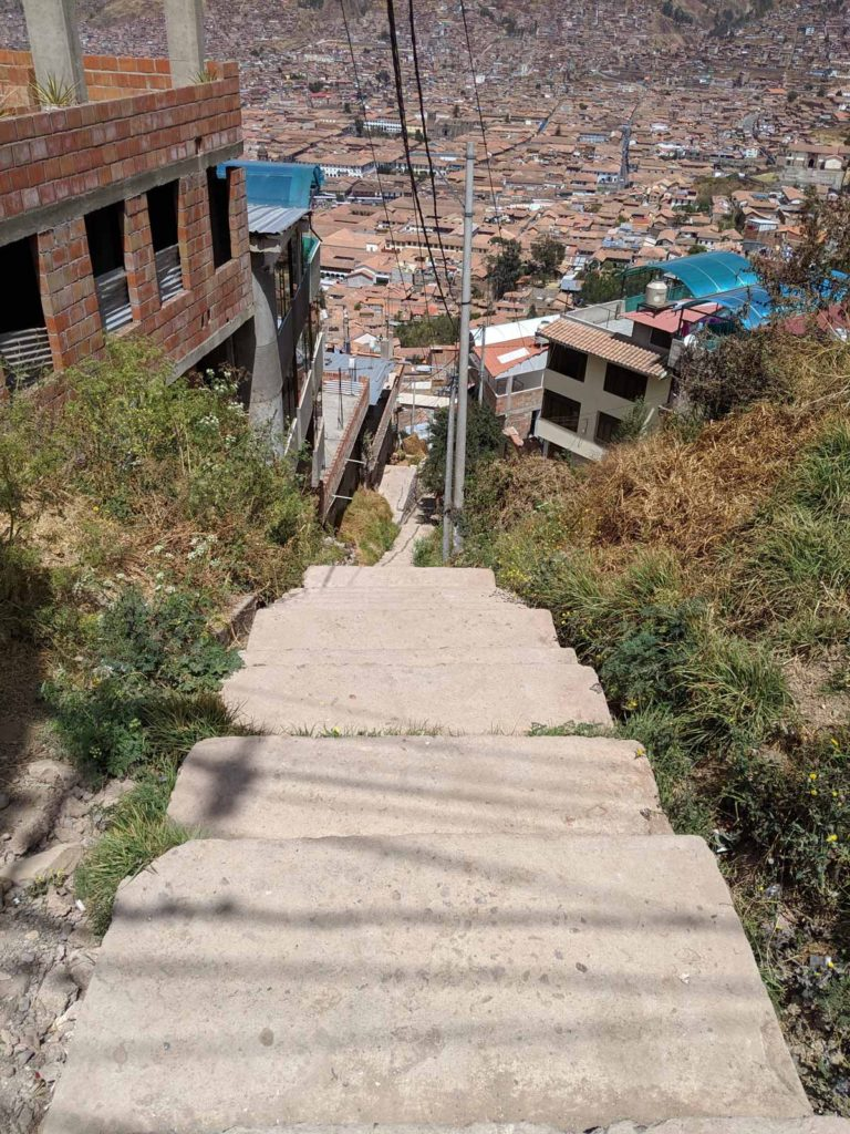 One of the many sets of stairs leading from our apartment all the way down to the city below. The photo shows the steep stairs and the city below, which appears very small.