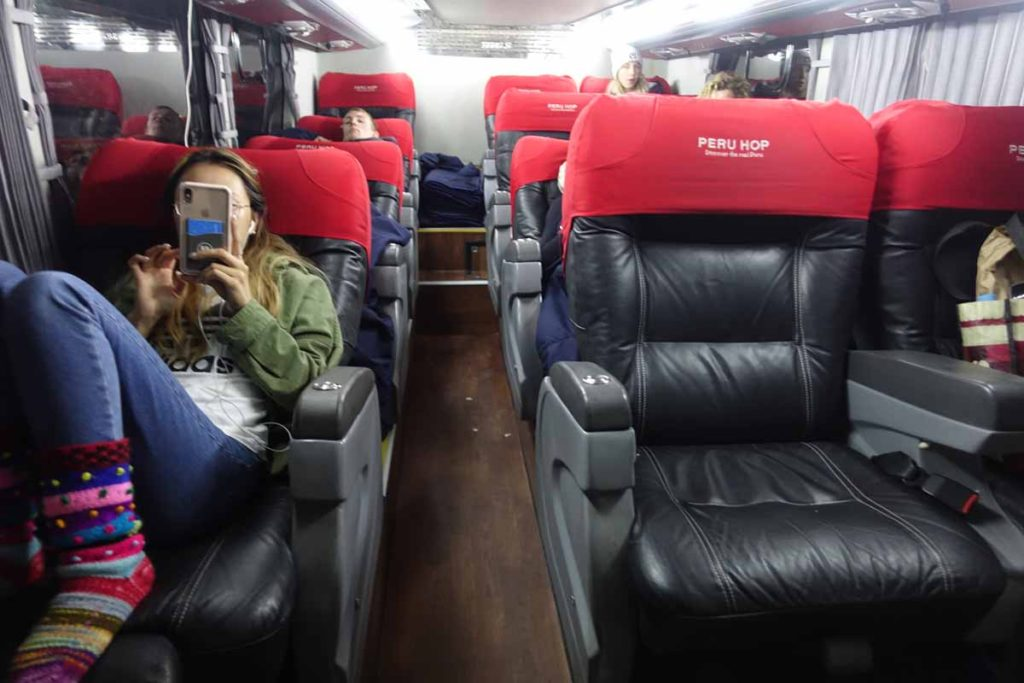 Inside a Peru Hop bus. A person reclining far back in a seat.