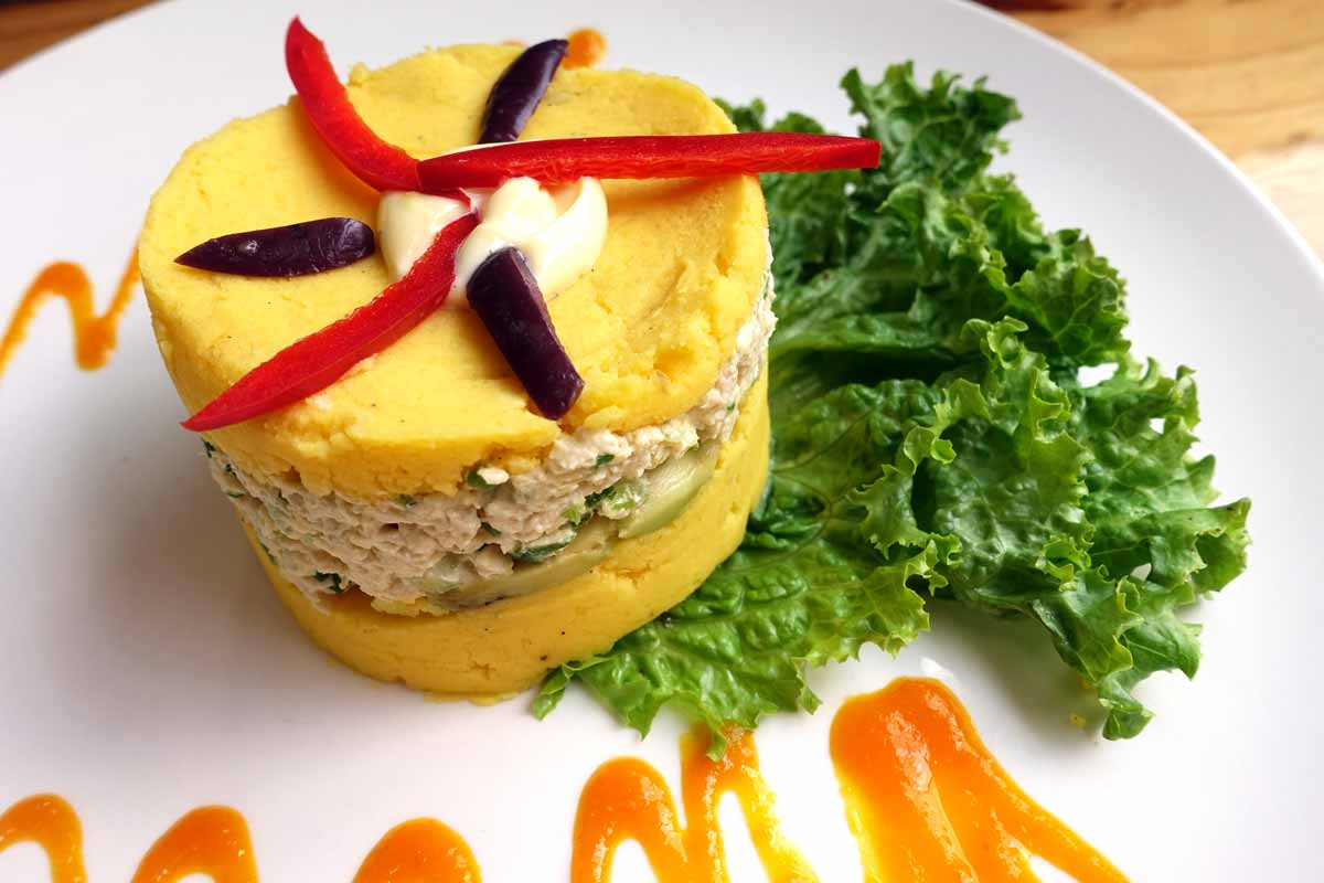 a cylindrical pile of yellow potatoes - made yellow by the addition of turmeric. Layer one is potatoes. Layer two is a sort of chicken salad. Layer three is more yellow potatoes. It's topped with peppers and black olives and served with an orange mango sauce.