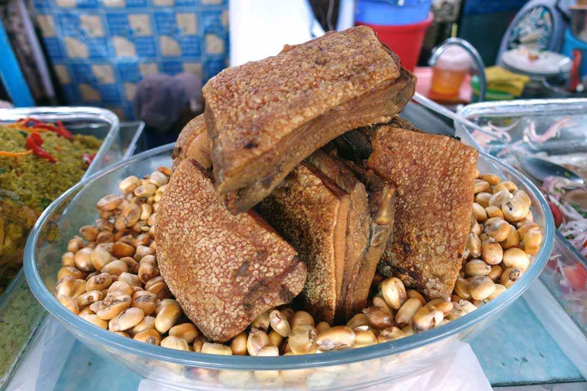 Chicharrón in a bowl that is also filled with deep fried corn.