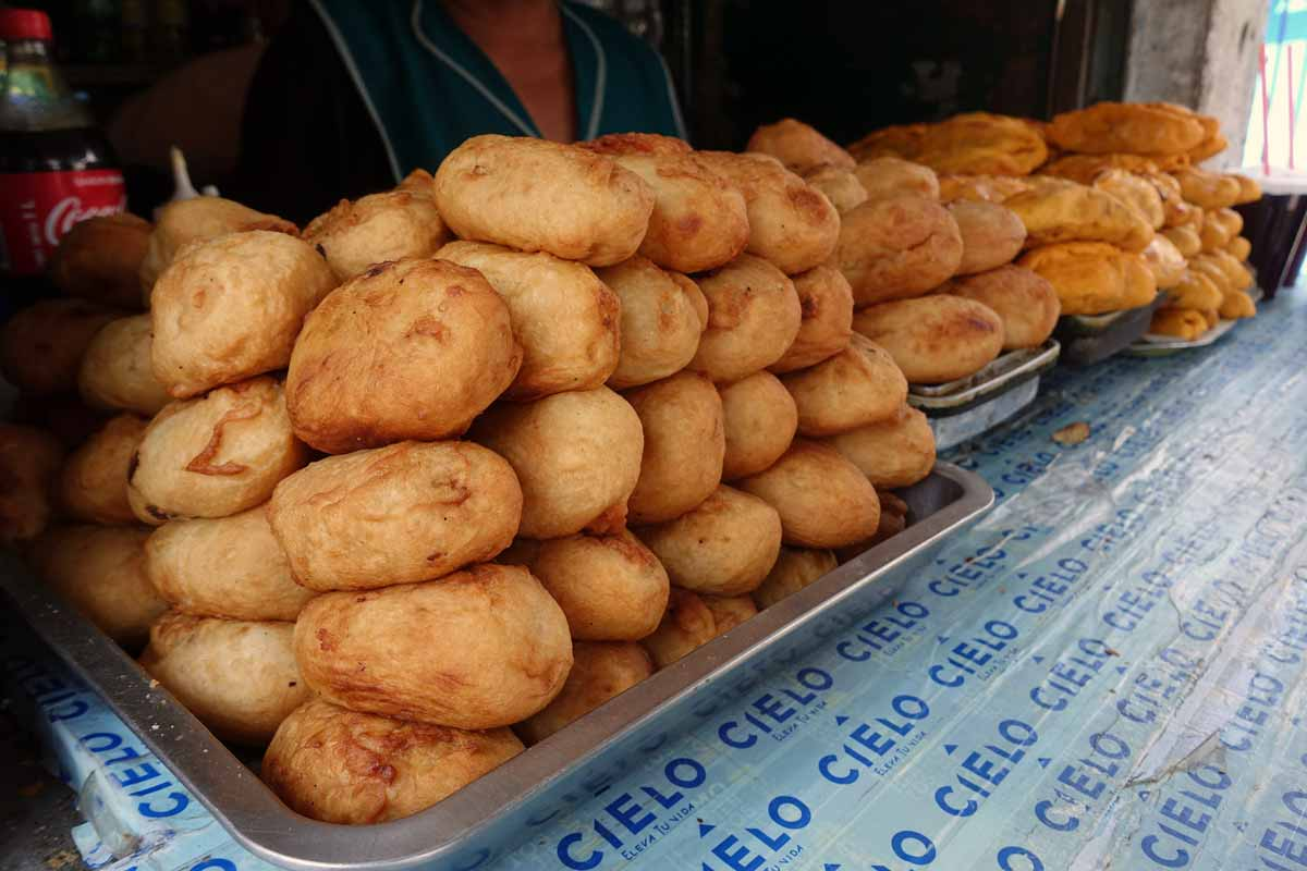 A tray piled with what looks like baked potatoes. But they are actually hand molded mashed potatoes deep fried to a crispy golden color.