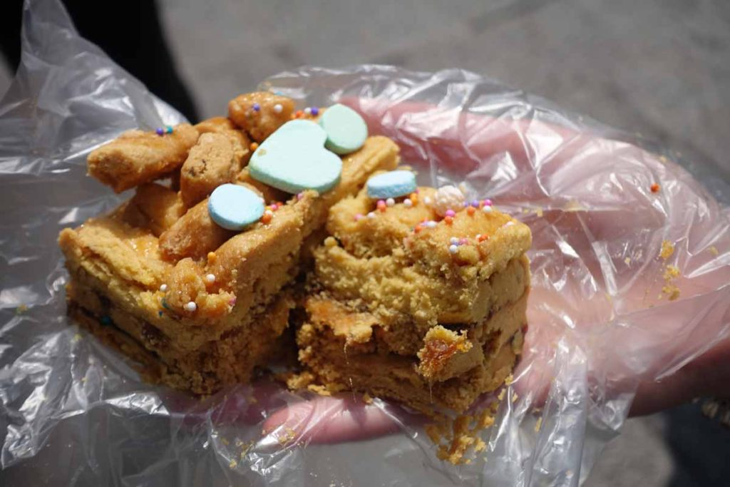 A Turrón de Doña Pepa. A light brown piece of  cake with something that looks like Sweet Tarts on top.