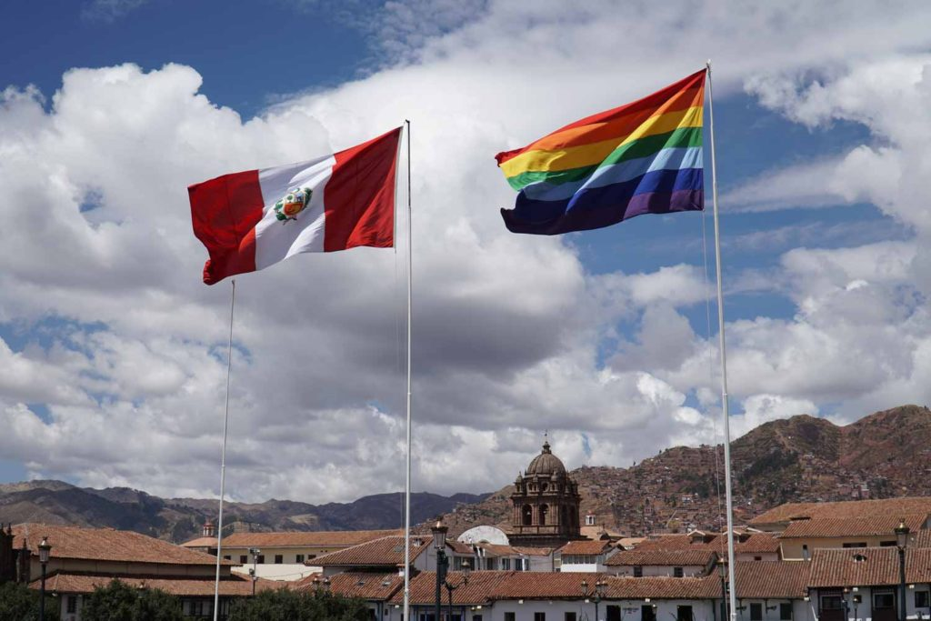 The Peru flag and the rainbow flag flying above cusco.