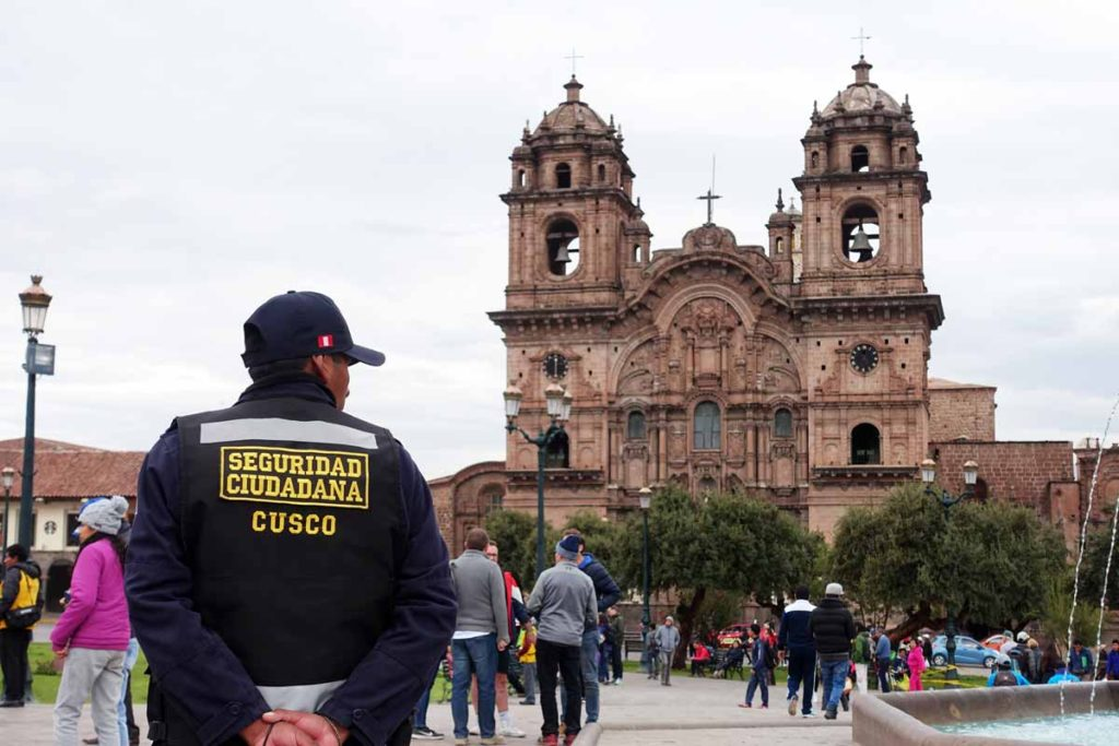 A Cusco security guard in uniform stands outside the cathedral on the Plaza de armas