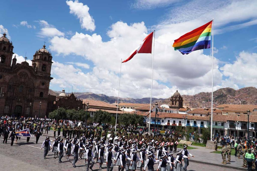 Civic group marching in the Sunday parade under the Peru and rainbow flags.