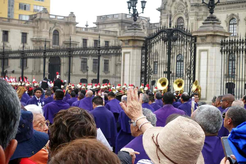 Men in purple robes marching through the street in Lima with a military band playing in the background.