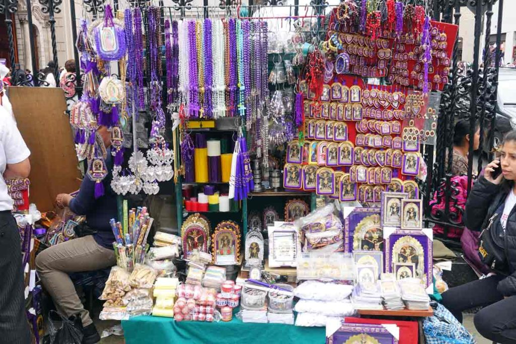 A vendor selling items related to the festival. Lots of purple beads, photos, and candles.