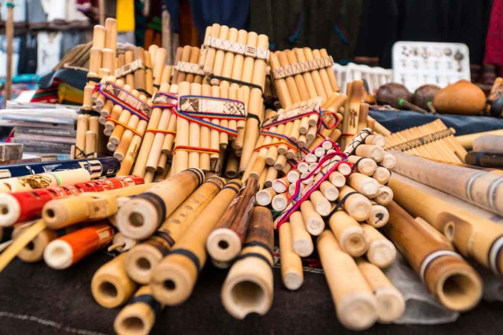Hand-carved music instruments at Pisac Market - regular flutes and pan flutes.