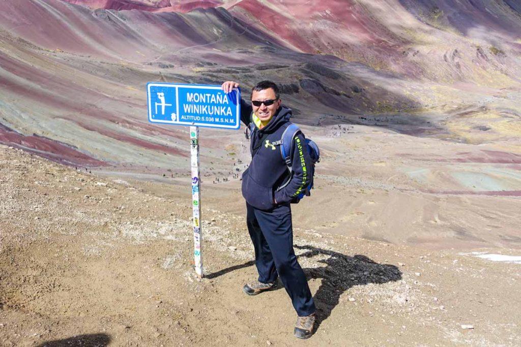 "Halef with a sign that says ""Montana Winikunka - altitud 5036 meters"""
