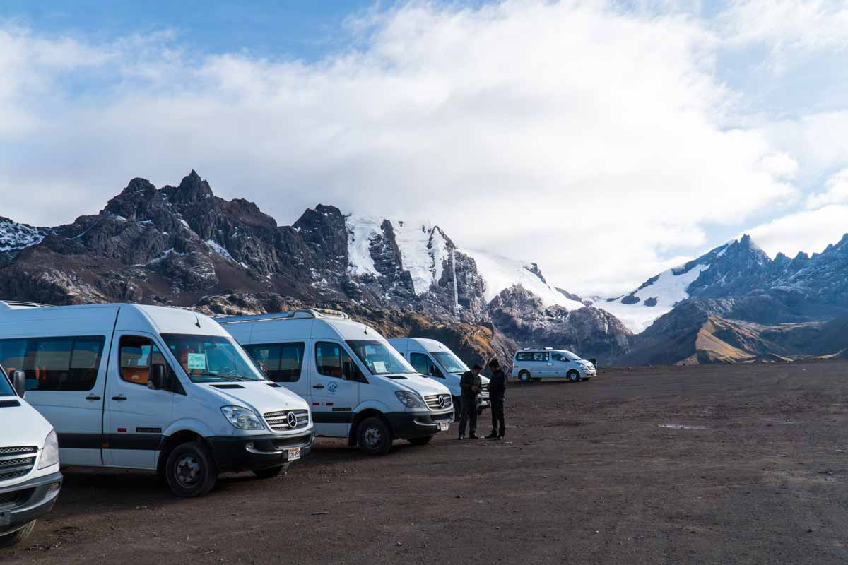 A gravel parking lot with white tourist vans and snow capped mountains in the background