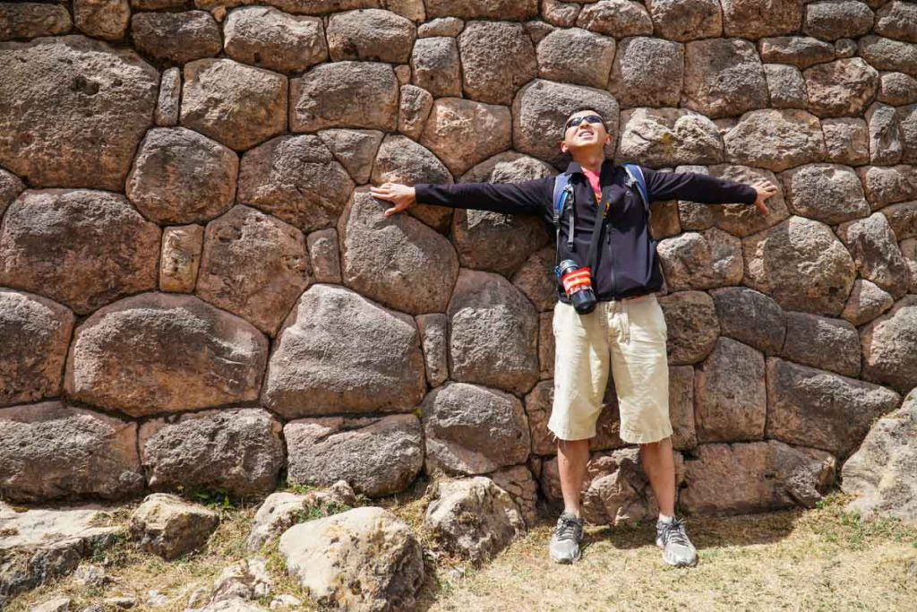 Halef standing in front of a wall at Puka Pukara. The rocks, although they fit together perfectly, are random.