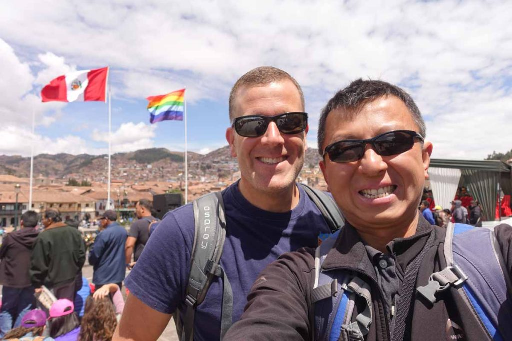Michael and Halef selfie in front of the Peruvian and Indigenous People's flags