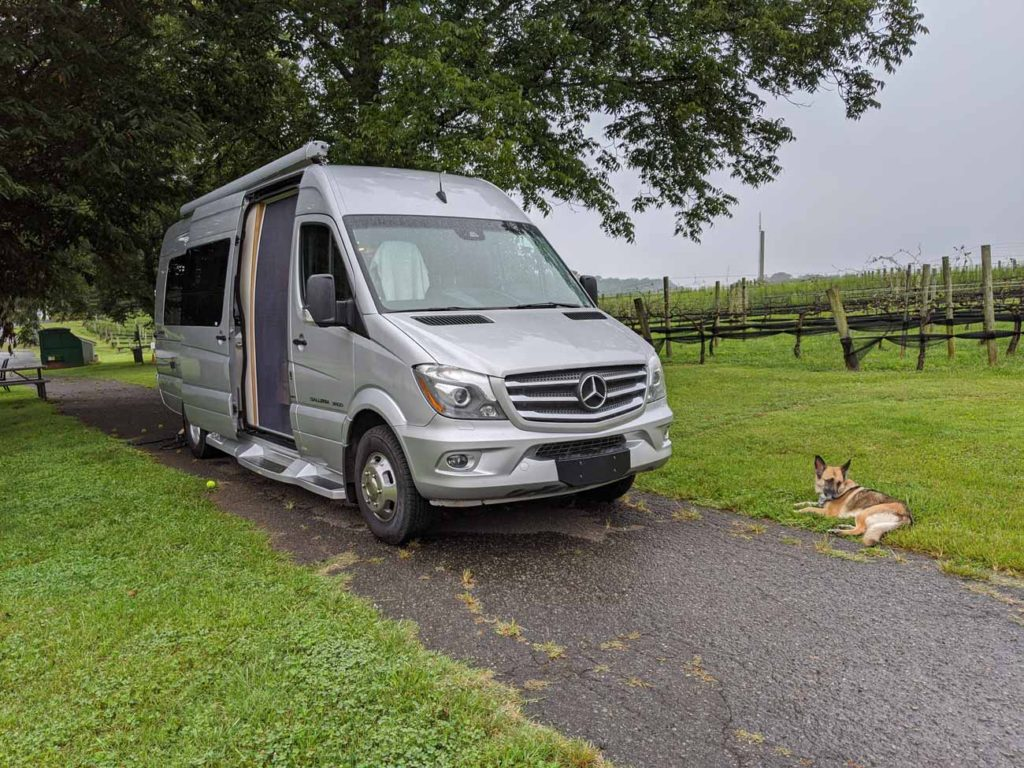 Our van parked on the lawn with a vineyard in the background and Kana, our dog, laying in the grass.
