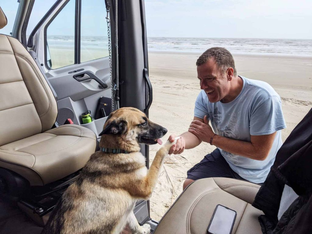 Beaches are great places to boondock. This is a photo of Michael and Kana in the van looking out over San Padre Beach in Texas