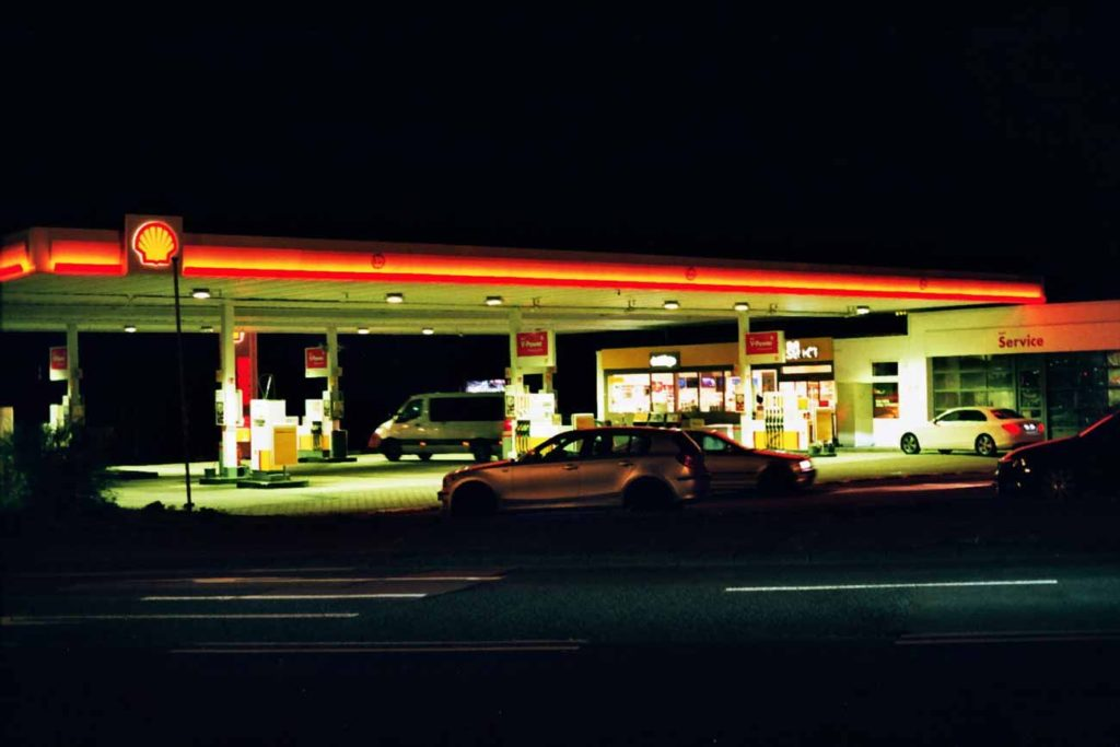 A shell station on the highway at night, courtesy of Unsplash.