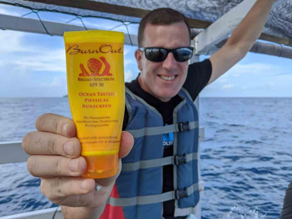 Michael holding a bottle of Burn Out sunscreen. We love this stuff.