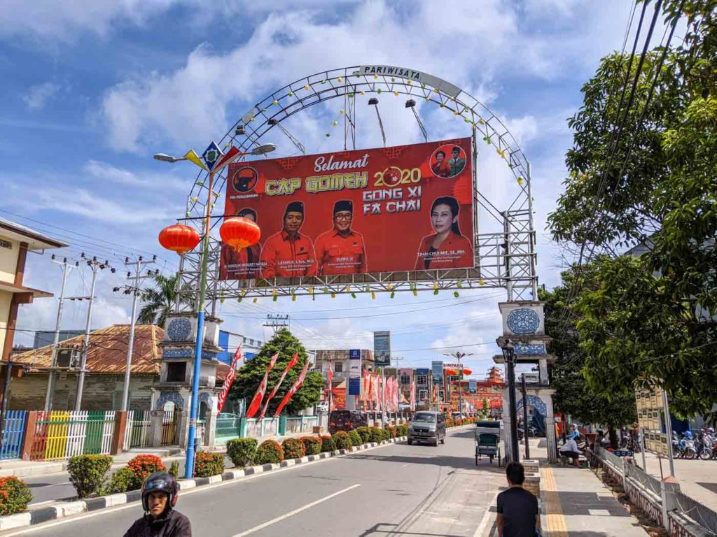 Singkawang Cap Go Meh festival banner over the parade route.