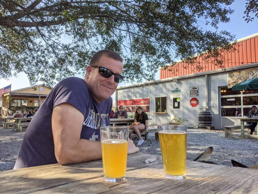 Michael sitting on a patio with two beers in front of him at Bayou Teche - our Harvest Host in Louisiana