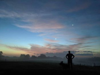 Michael and Kana, in silhouette on a field in the morning