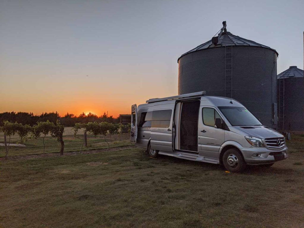 Our Coachmen Galleria parked next to a silo with a sunset and a vineyard in the background