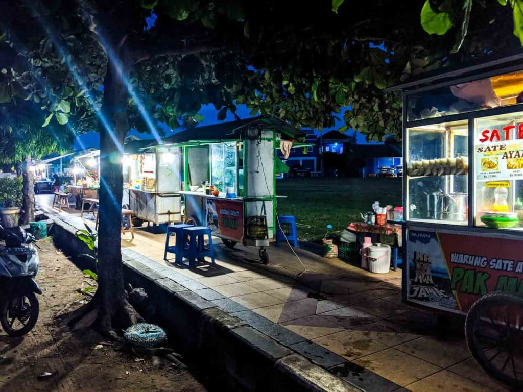 A line of food stalls on the square in Karimunjawa, including one that serves authentic Indonesian sate.