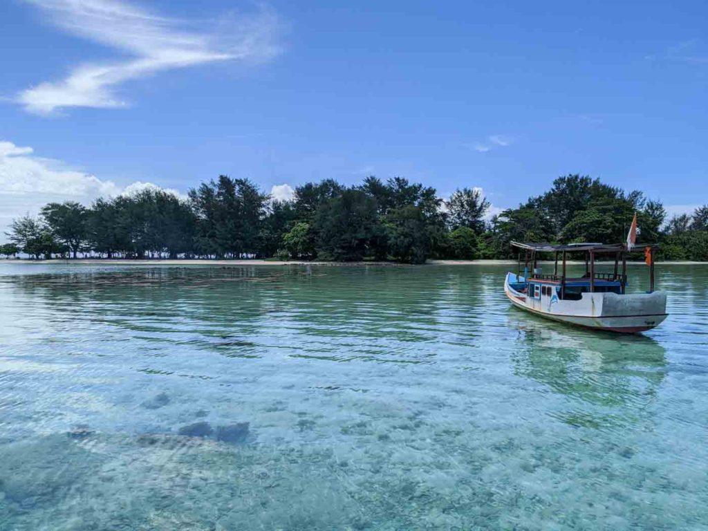 A wooden boat in glassy water just off an island near Karimunjawa