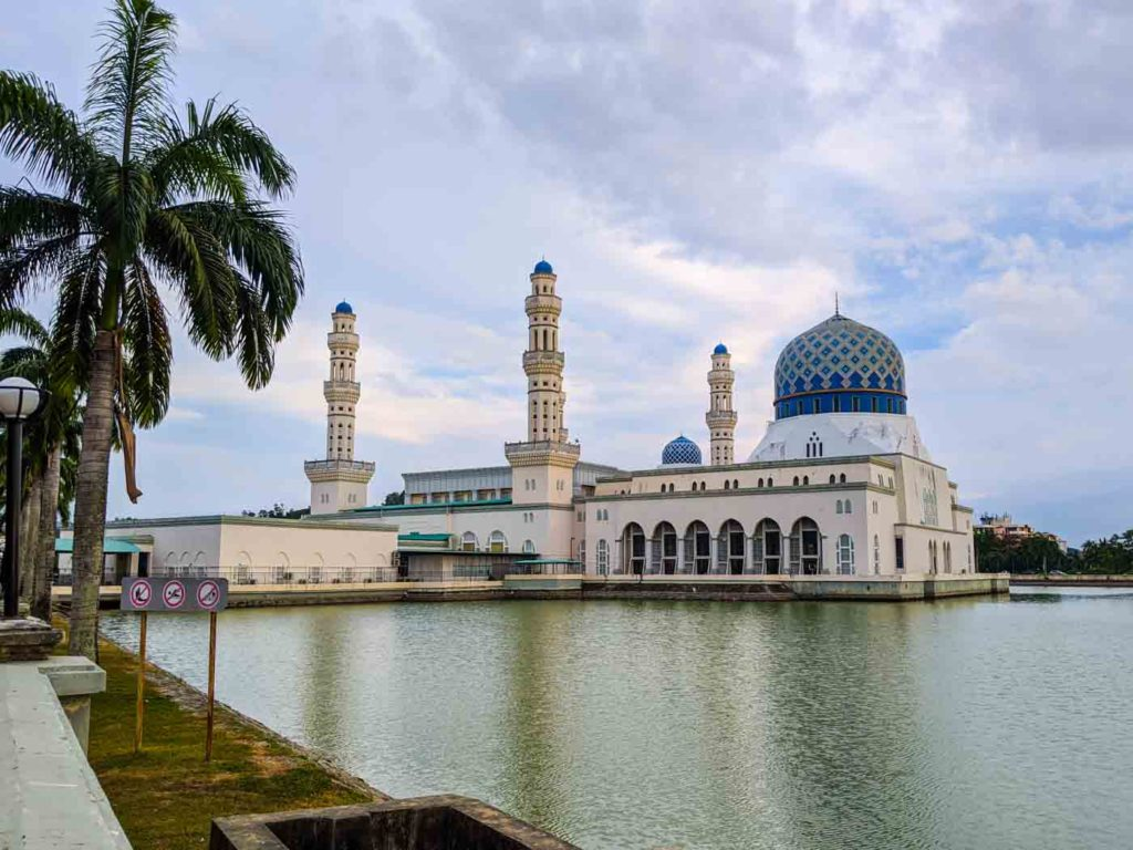 The exterior of he Kota Kinabalu City mosque with 4 minarets surrounded by a large moat