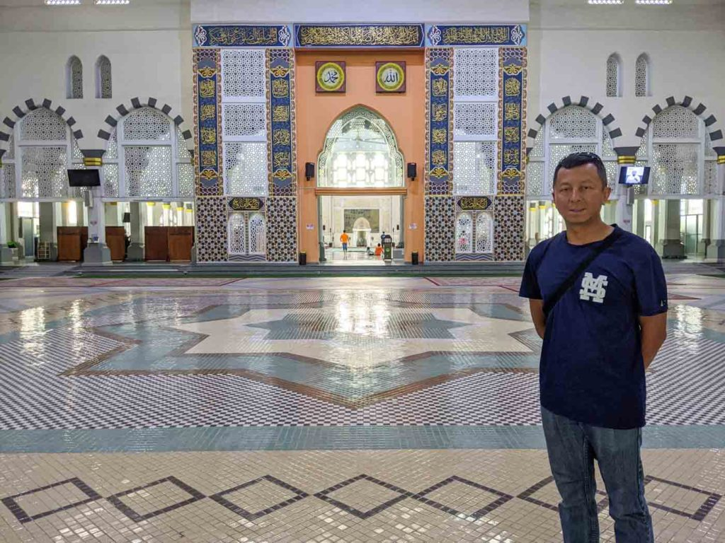 Interior of the Kota Kinabalu cuty mosque with Halef int he foreground. Behind him is the area in which people pray