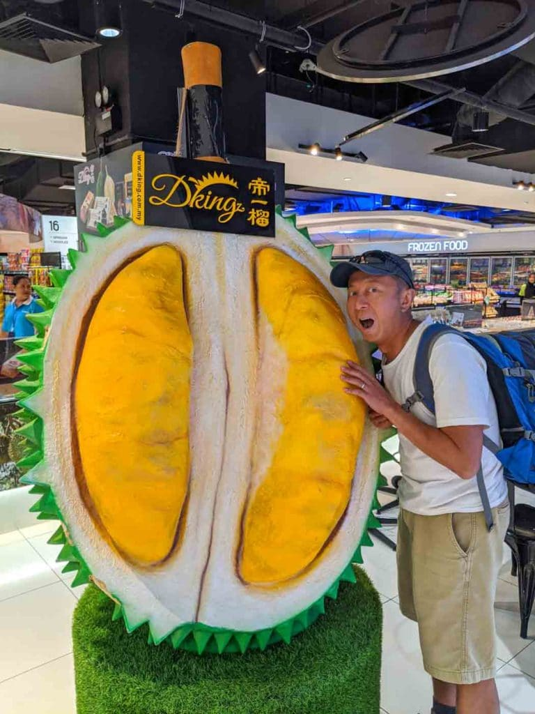 Eating durian is one of the top things to do in Kota Kinabalu. This is Halef beside a large sculpture of a durian in a market.