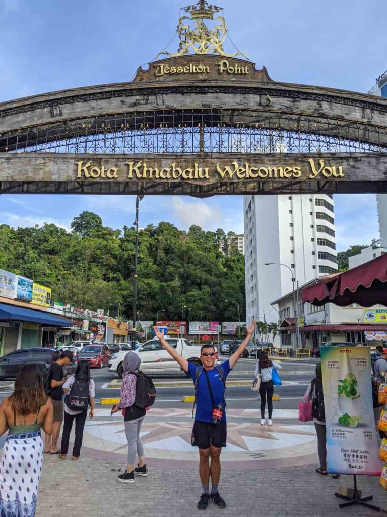 "Halef standing in front of the sign for Jesselton Wharf. The sign says ""Kota Kinabalu Welcomes You"""
