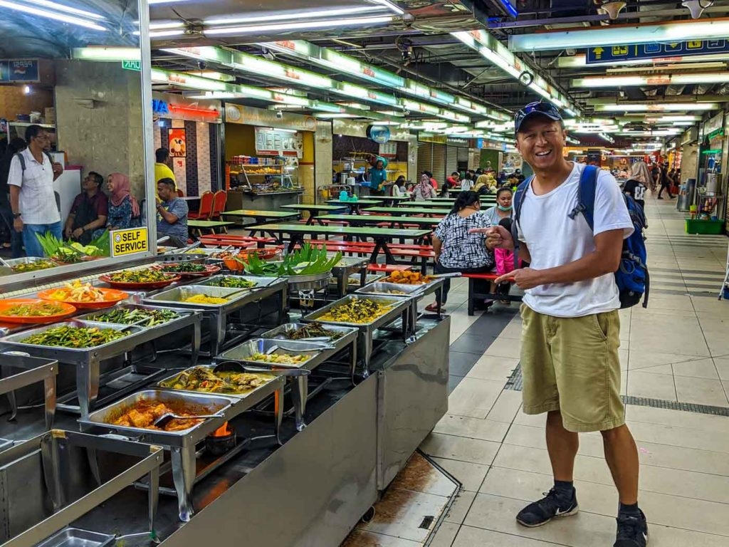 One of our top Kota Kinabalu travel tips is to eat at the mall. This is the food court in the basement of Centre Point mall in Kota Kinabalu. Halef is standing at the self-serve food table at a restaurant there. There are dozens of dishes.