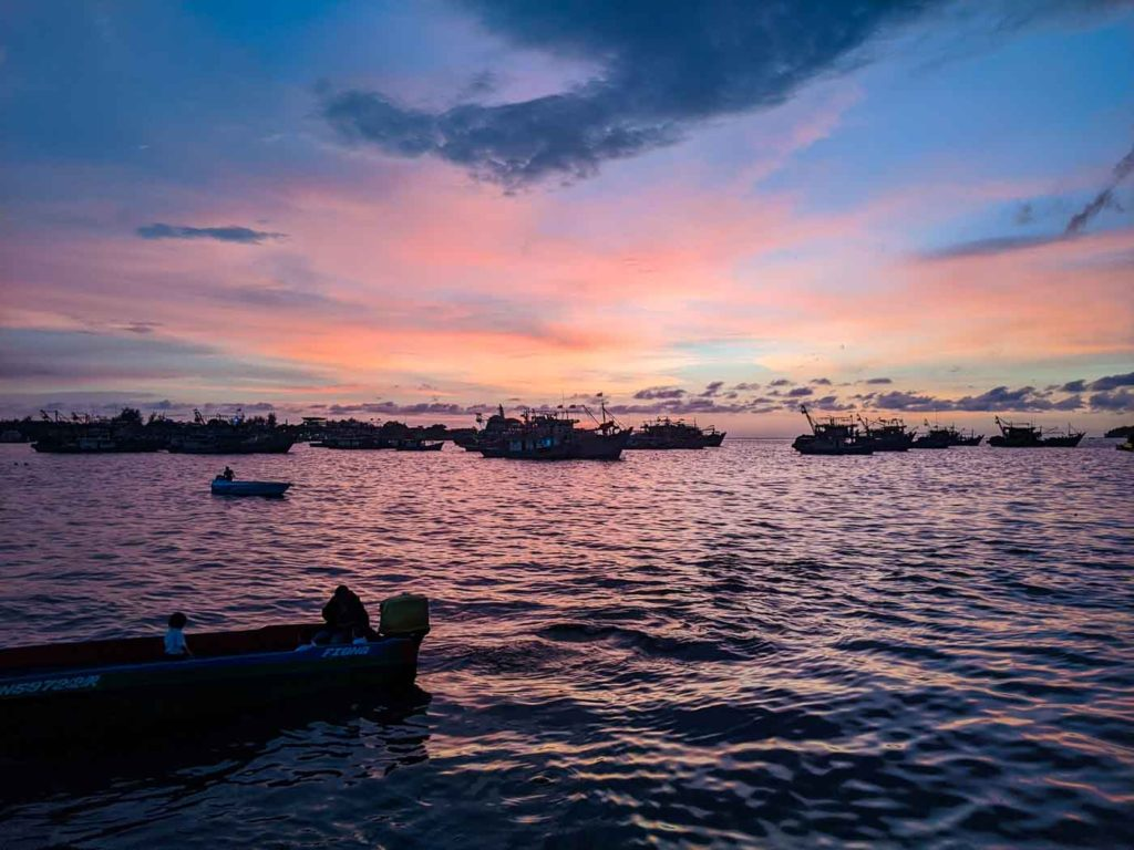 Sunset in Kota kinabalu with pinks and blues and silhouettes of several boats in the foreground